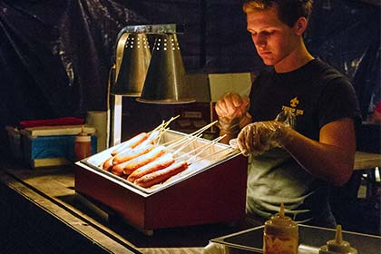A vendor places corn dogs under a heat lamp at the food court.