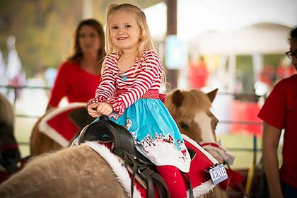 A girl riding one of the ponies at the Sights & Sounds petting zoo.
