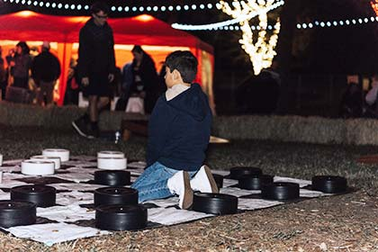 A boy sits on the giant Checkers board.